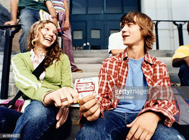 Teenage Girl Passes an Envelope to a Teenage Boy as They Sit on the Steps at a Secondary School Entrance Together