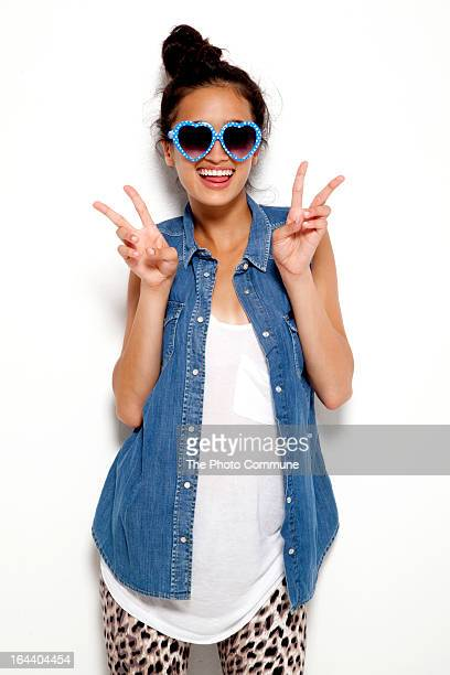 Teenage girl peace signs in heart shape glasses