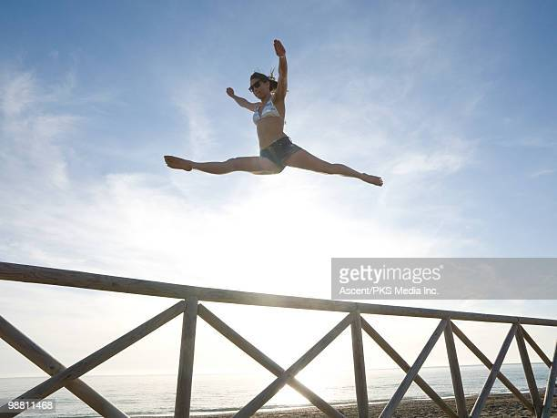 teenage girl performs jump split above rail, beach - doing the splits stock pictures, royalty-free photos & images