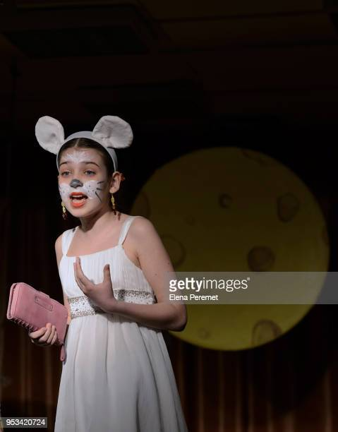 A teenage girl performs on stage in a play