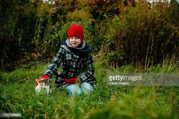 a teenage girl petting her cat in a field in michigan - cat with red hat stock pictures, royalty-free photos & images