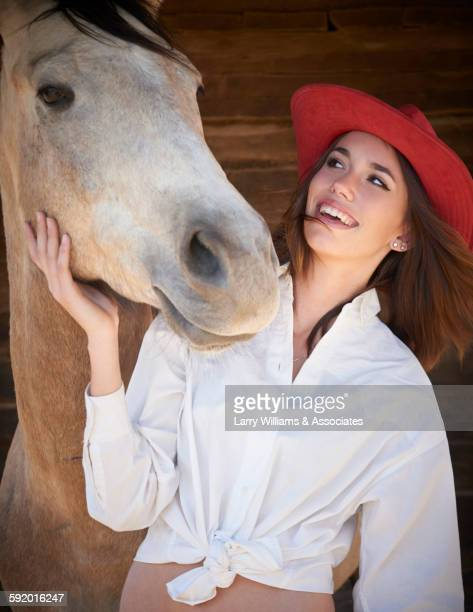 teenage girl petting horse by wooden wall - girl blowing horse - fotografias e filmes do acervo
