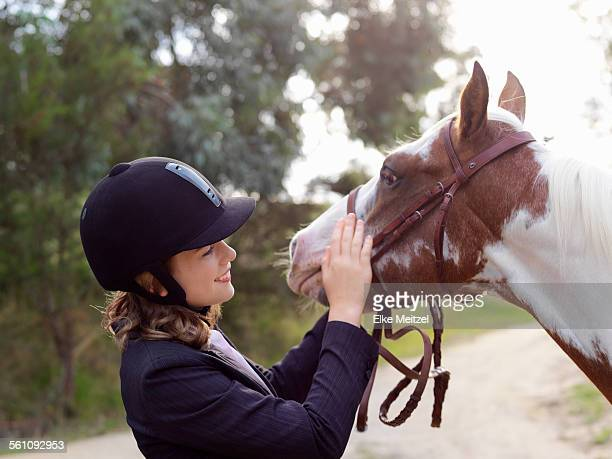 teenage girl petting horse - riding hat stock pictures, royalty-free photos & images