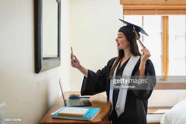 Teenage girl phone chatting wearing cap and gown