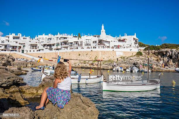 Teenage girl photographing Binibequer Vell at Menorca