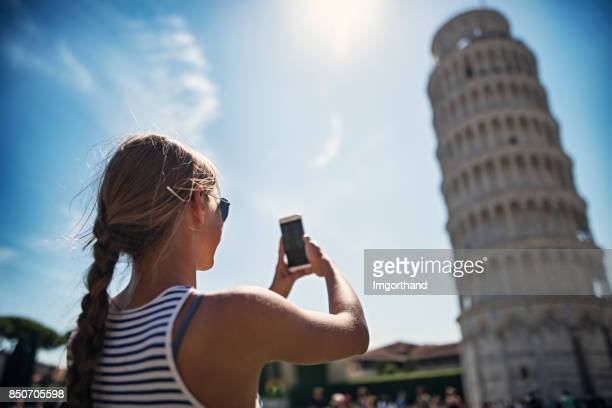 teenage girl photographing the leaning tower of pisa - leaning tower of pisa stock pictures, royalty-free photos & images