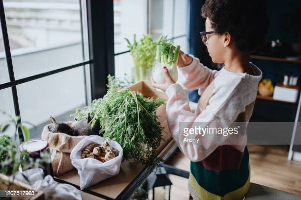 Teenage girl placing groceries to wooden baskets