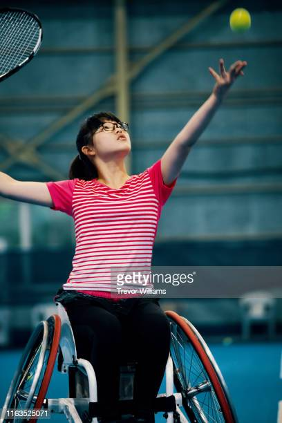 teenage girl playing a wheelchair tennis match at an indoor tennis court - 車いすテニス ストックフォトと画像