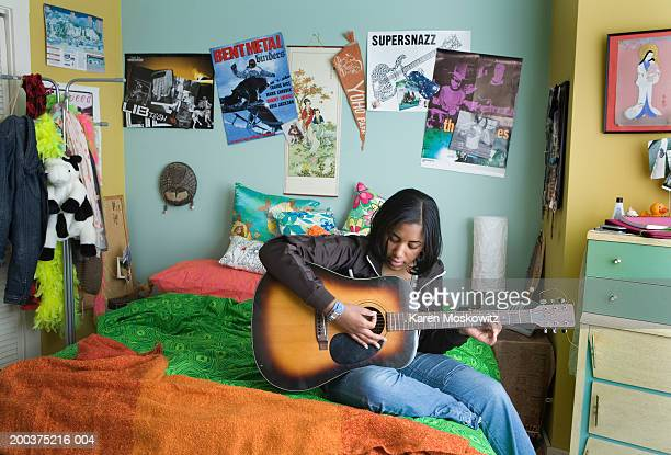 Teenage girl (15-17) playing acoustic guitar on bed