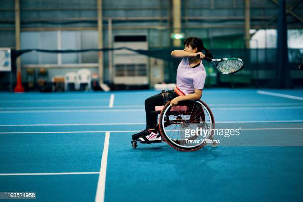 teenage girl playing and practicing wheelchair tennis at an indoor tennis court - 車いすテニス ストックフォトと画像