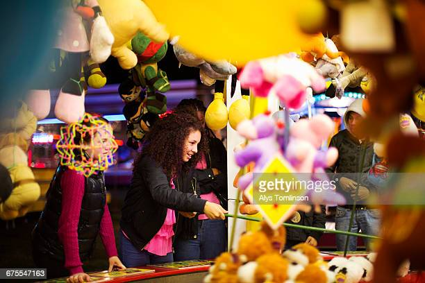 teenage girl playing at fairground stall - carnival stock pictures, royalty-free photos & images