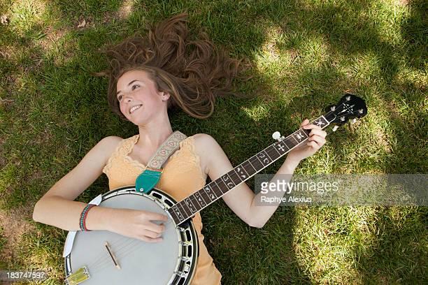 Teenage girl playing banjo on grass, overhead view