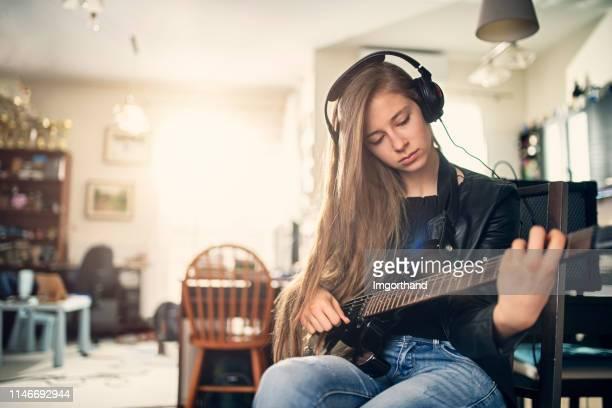 エレキギターを弾く十代の少女 - ベースギター ストックフォトと画像