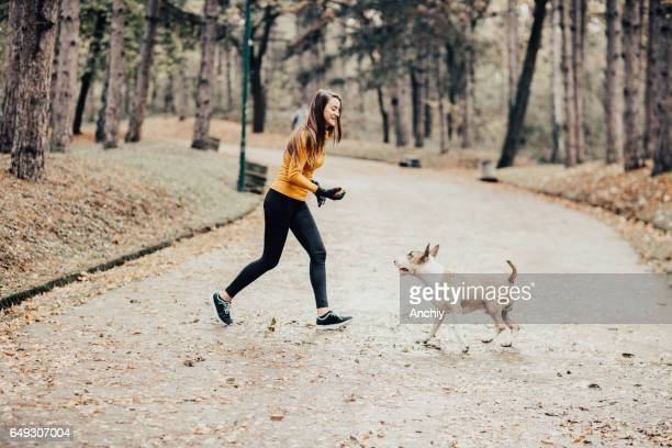 Teenage girl playing fetch with her dog
