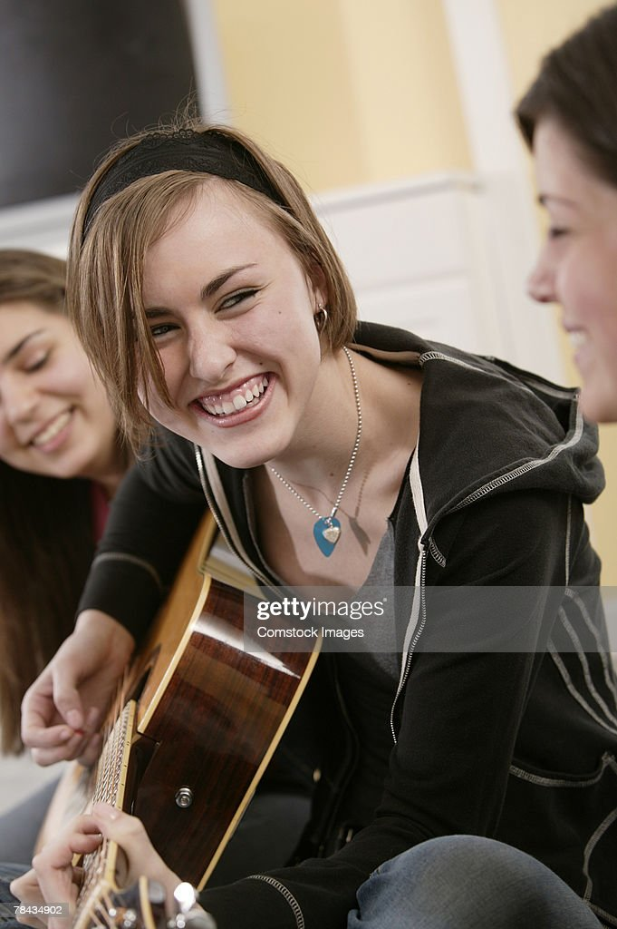 Teenage girl playing guitar with friends : Stockfoto