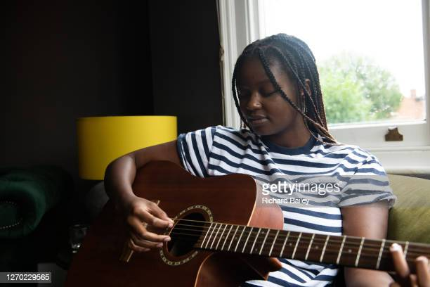 teenage girl playing her guitar - guitarist stock pictures, royalty-free photos & images