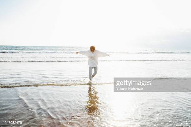 a teenage girl playing on the water's edge - yusuke nishizawa stock pictures, royalty-free photos & images