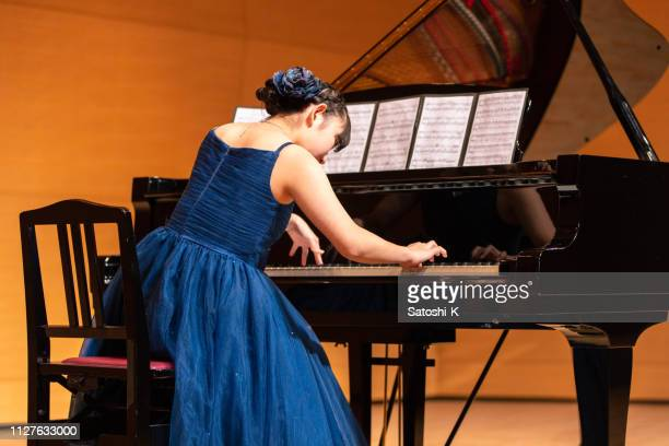 teenage girl playing piano at concert hall - classical musician stock pictures, royalty-free photos & images