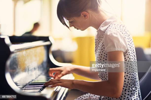 Teenage girl playing piano concert