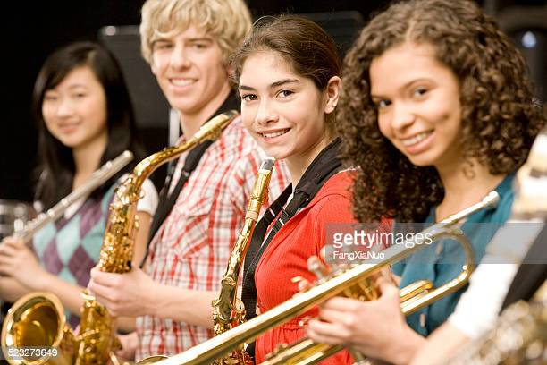 teenage girl playing saxophone in band - performance group stock pictures, royalty-free photos & images