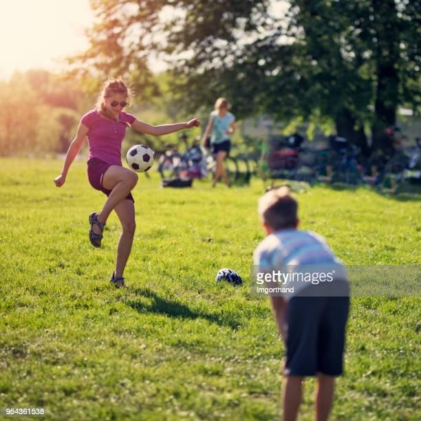 adolescente jugando al fútbol con su hermano. - mama futbol fotografías e imágenes de stock