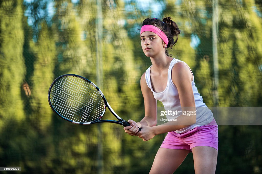 Teenage girl playing tennis and waiting for the ball. : Stock Photo