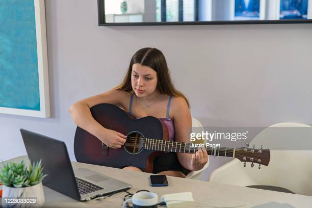 teenage girl playing the guitar at home. she is using following an online tutorial - songwriter stock pictures, royalty-free photos & images