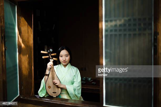 teenage girl playing the lute at window - chinese music stock pictures, royalty-free photos & images