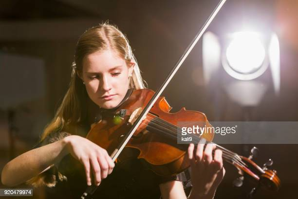 Teenage girl playing the violin in concert