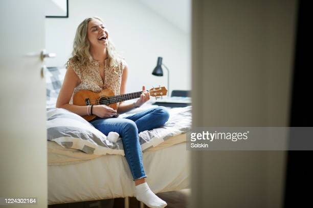teenage girl playing ukulele in her room - acoustic guitar stock pictures, royalty-free photos & images