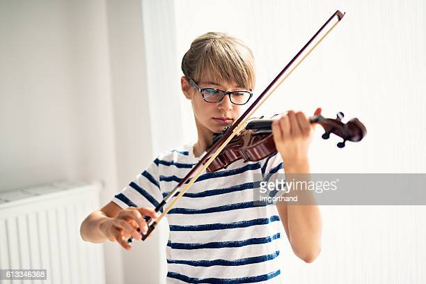 Teenage girl playing violin at home