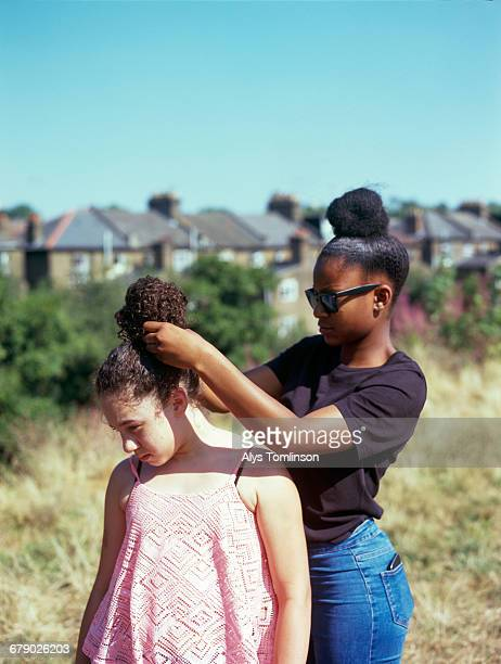 Teenage girl playing with her friend's hair