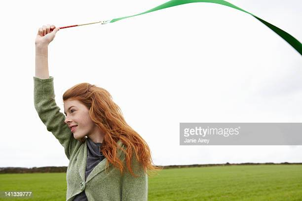 teenage girl playing with ribbon - streamer stock photos and pictures