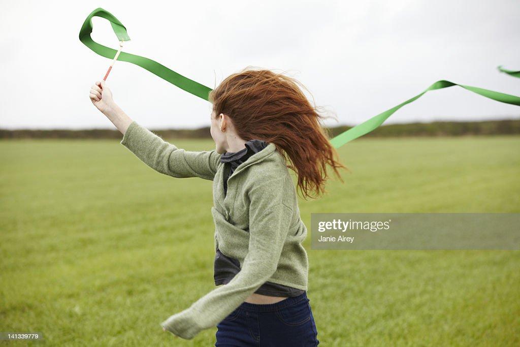Teenage girl playing with ribbon : Bildbanksbilder