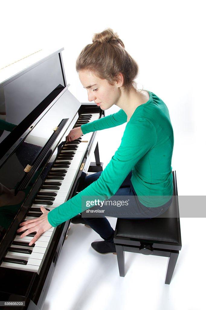 teenage girl plays piano in green shirt : Stock Photo