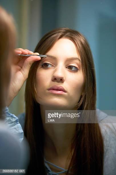 Teenage girl (16-18), plucking eyebrows