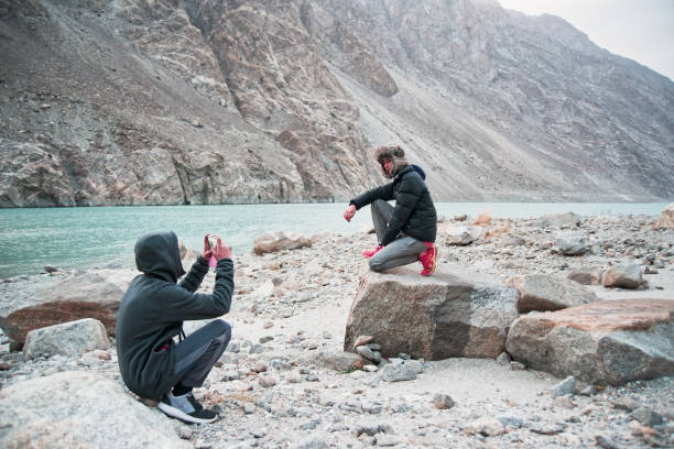Teenage girl poses for phone portrait taken by brother beside Indus river