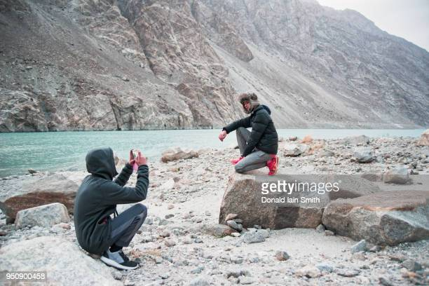 teenage girl poses for phone portrait taken by brother beside indus river - etnia indo asiatica foto e immagini stock