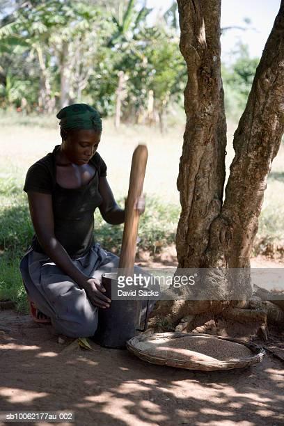 Teenage girl (16-17) pounding millet