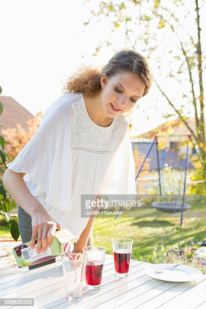 teenage girl pouring fruit juice at patio table - drinks carton stock pictures, royalty-free photos & images