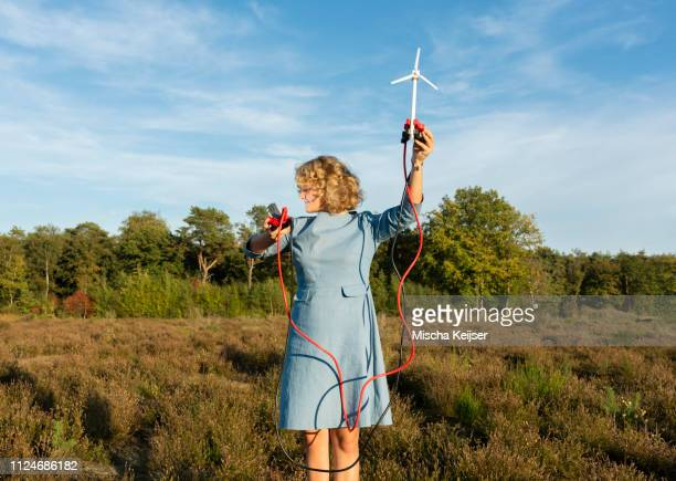 teenage girl powering led light using miniature wind turbine, netherlands - environmentalist stock pictures, royalty-free photos & images