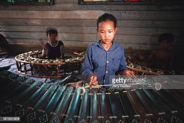 A teenage girl practices a traditional Cambodian bamboo xylophone at Homeland The group tries to give older orphans some small skills they can use to...