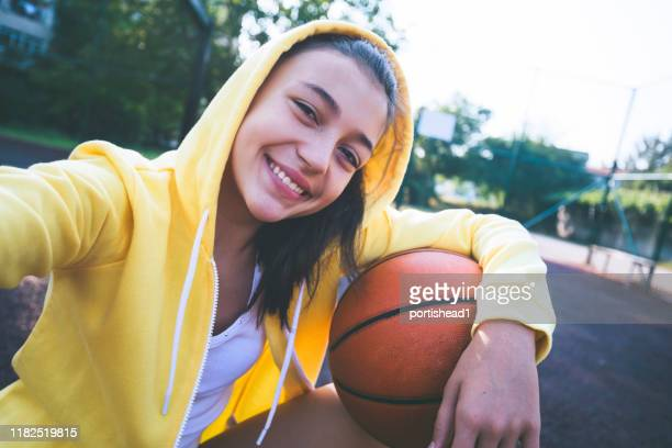 teenage girl practicing basketball and making selfie - basketball player stock pictures, royalty-free photos & images