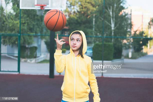 teenage girl practicing basketball - sweatshirt stock pictures, royalty-free photos & images