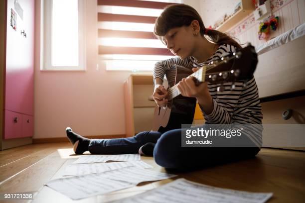 teenage girl practicing guitar at home - pizzicare le corde di uno strumento foto e immagini stock