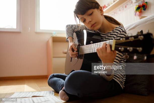 teenage girl practicing guitar - plucking an instrument stock pictures, royalty-free photos & images