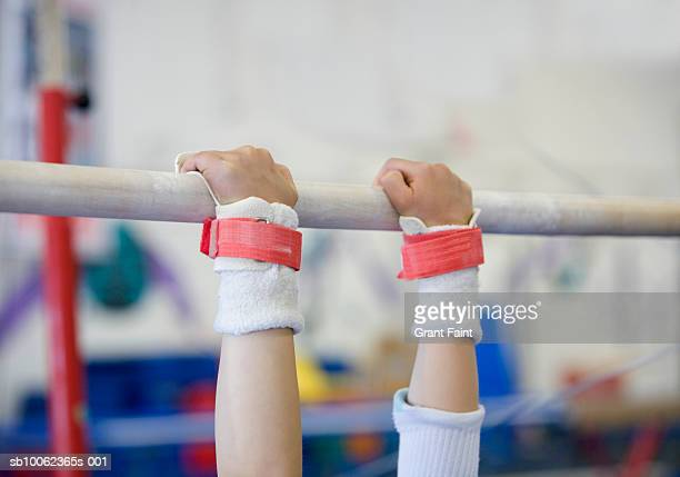 teenage girl (16-17 years) practicing on uneven bars, close-up of hands - horizontal bars stock pictures, royalty-free photos & images