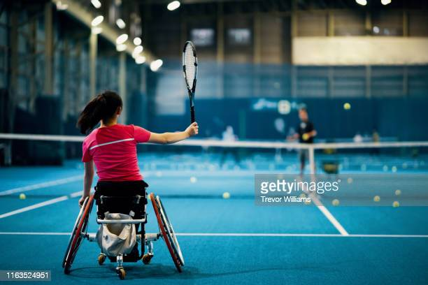 teenage girl practicing wheelchair tennis together with her coach at an indoor tennis court - ラケット ストックフォトと画像