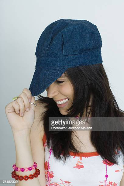 'Teenage girl pulling cap down, smiling, portrait'