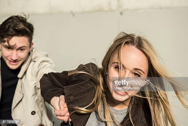 'Teenage girl pulling her boyfriend with his hand, Munich, Bavaria, Germany'